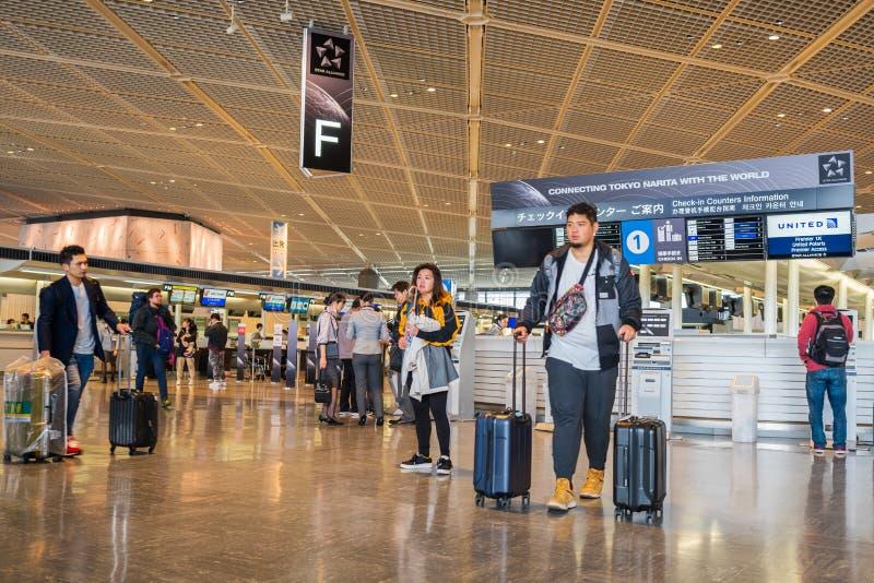 Os passageiros andam ao redor na ?rea da partida do terminal 1 no aeroporto internacional de Narita, T?quio, Jap?o imagem de stock