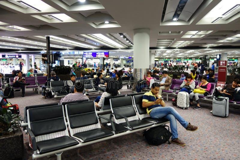 Os passageiros esperam o voo do trânsito a entrada do aeroporto de Hong imagens de stock