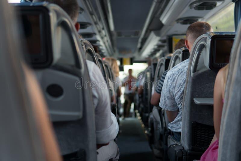 Os passageiros no ônibus durante a viagem com turistas e excursão guiada foto de stock