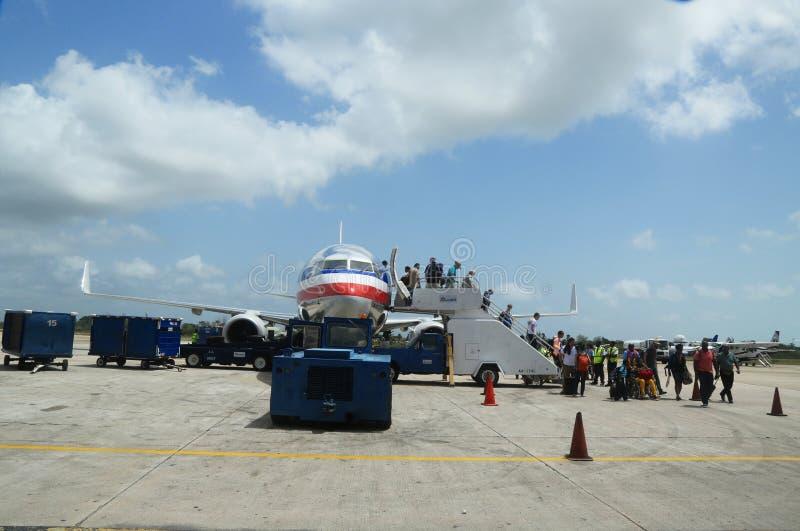 Os passageiros que desembarcam o plano de American Airlines aterraram em Philip Goldson Airport em Belize imagens de stock