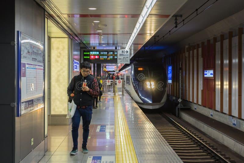 Os passageiros que esperam Keisei Skyliner treinam no aeroporto internacional de Narita fotos de stock