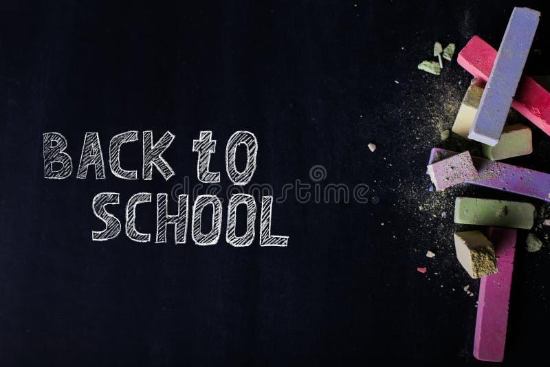 Os past?is coloridos encontram-se em um quadro preto, espa?o da c?pia O conceito da escola, da educa??o e da inf?ncia foto de stock royalty free