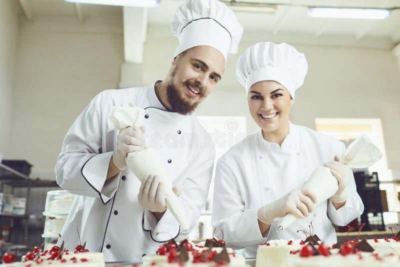 Os pasteleiros com um saco para o creme decorarão o bolo fotografia de stock