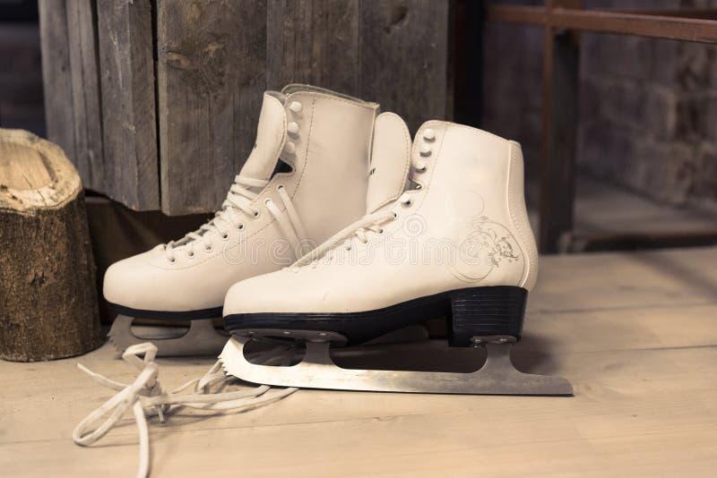 Os patins brancos das mulheres estão no assoalho feminine para patinar Esporte de inverno foto de stock royalty free