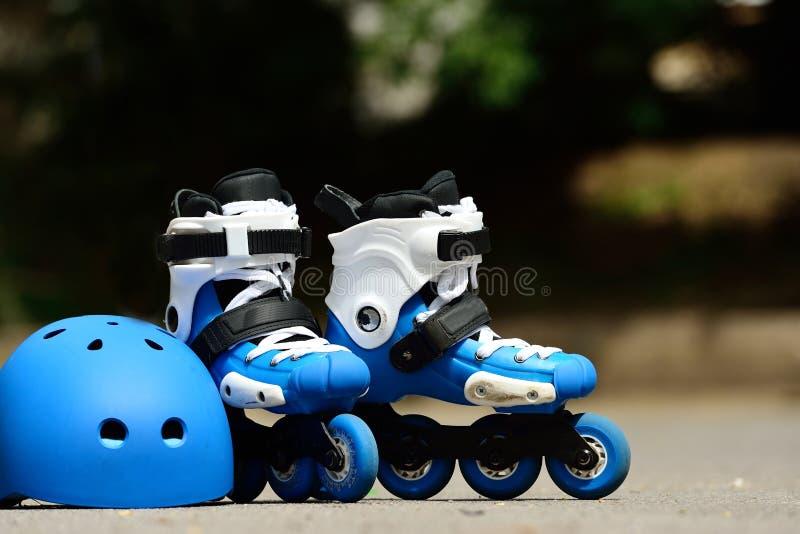 Os patins inline do rolo com o capacete no patim estacionam no fundo cinzento do asfalto fotos de stock royalty free