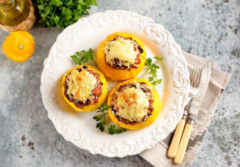 Os patissons amarelos orgânicos enchidos com carne, cebolas, cenouras, cogumelos e pimenta vermelha cozeram no forno com queijo imagens de stock royalty free