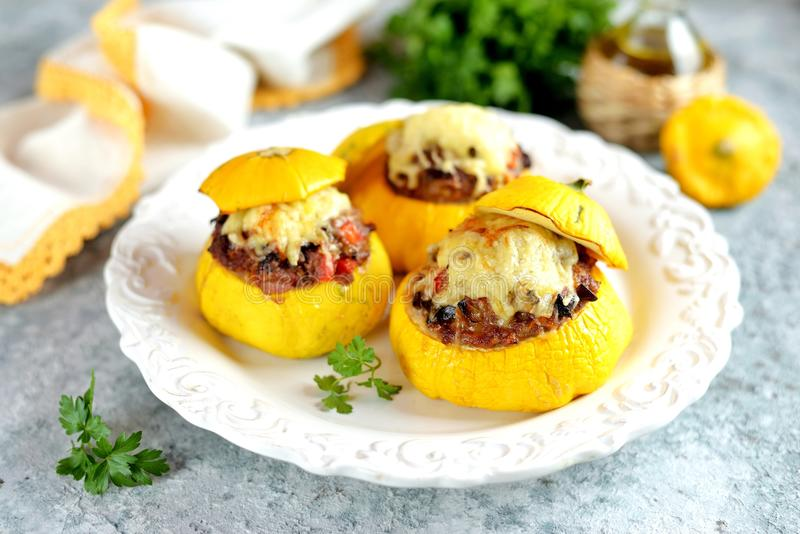 Os patissons amarelos orgânicos enchidos com carne, cebolas, cenouras, cogumelos e pimenta vermelha cozeram no forno com queijo fotografia de stock