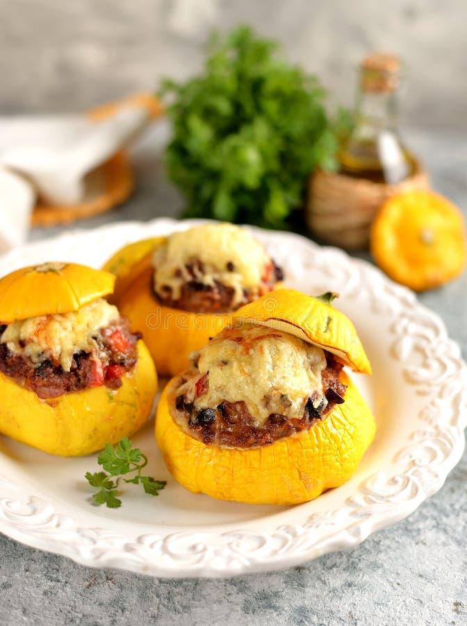 Os patissons amarelos orgânicos enchidos com carne, cebolas, cenouras, cogumelos e pimenta vermelha cozeram no forno com queijo fotos de stock