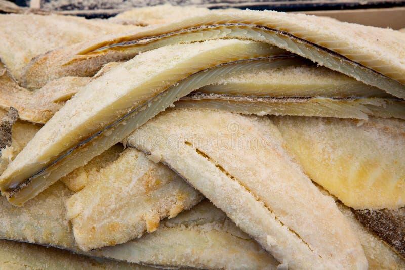 Os peixes de bacalhau salgaram os bacalhaus em seguido empilhados fotografia de stock