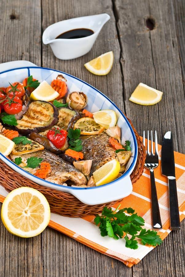 Os peixes do Seabass cozeram com vegetais, ervas e limão foto de stock