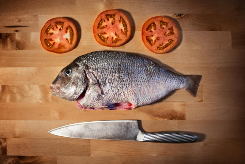 Os peixes frescos deliciosos do sargo na cozinha de madeira embarcam fotografia de stock royalty free