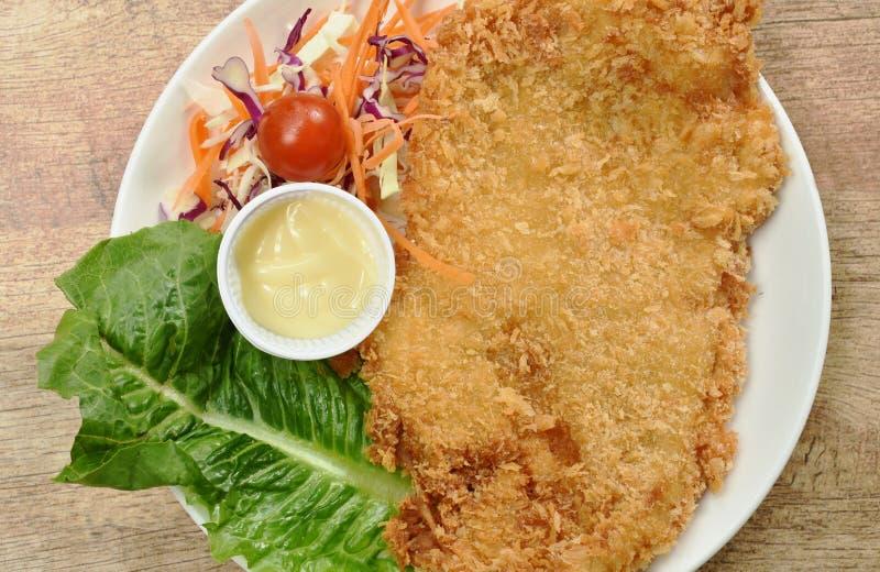 Os peixes fritados massa da zorra envolveram o bife do pão com salada no prato foto de stock