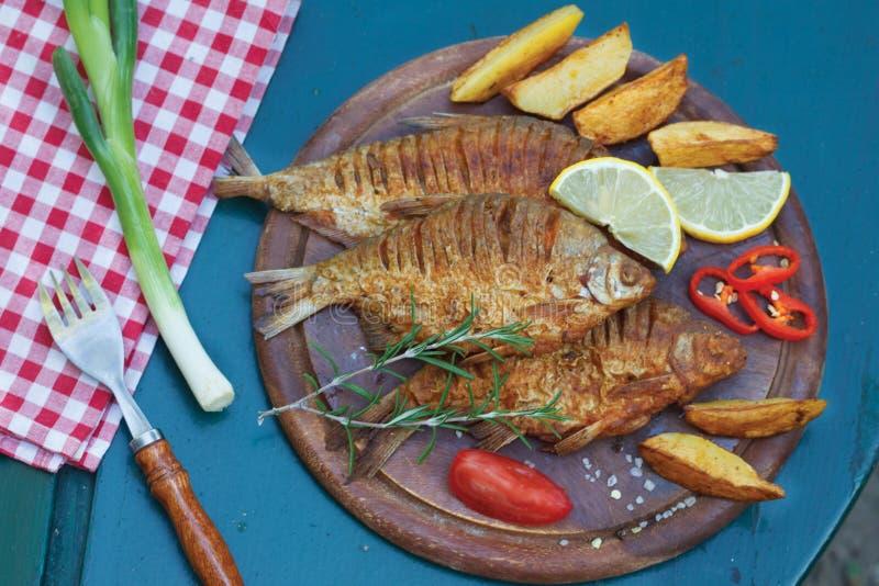 Os peixes fritados serviram em uma placa de madeira com batata imagens de stock royalty free