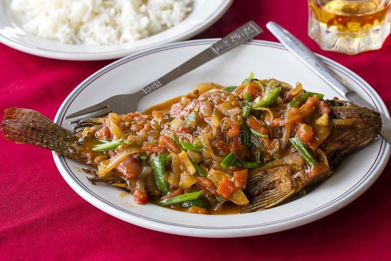 Os peixes picantes da carpa fritaram no molho com os vegetais servidos na placa no restaurante asiático Prato burmese tradicional imagem de stock royalty free