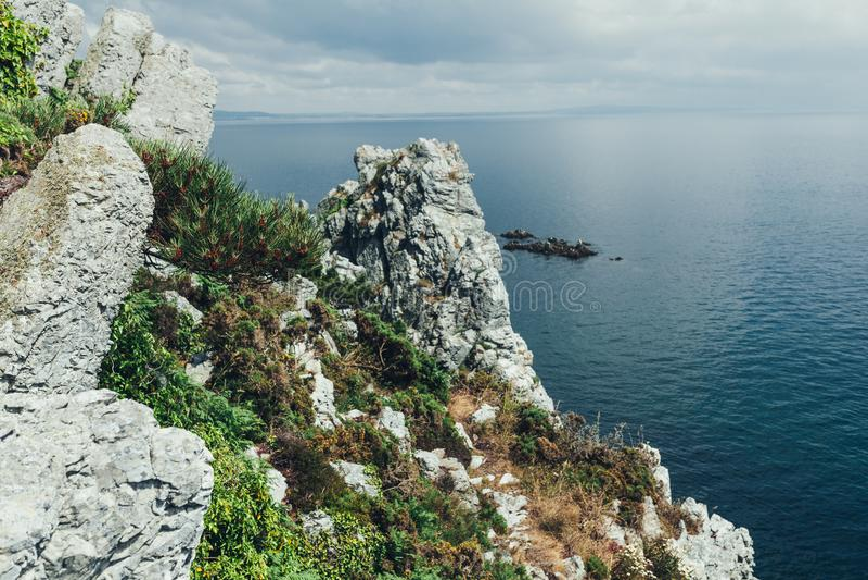 Os penhascos afiados penduram sobre o oceano, fundo marinho dramático foto de stock royalty free
