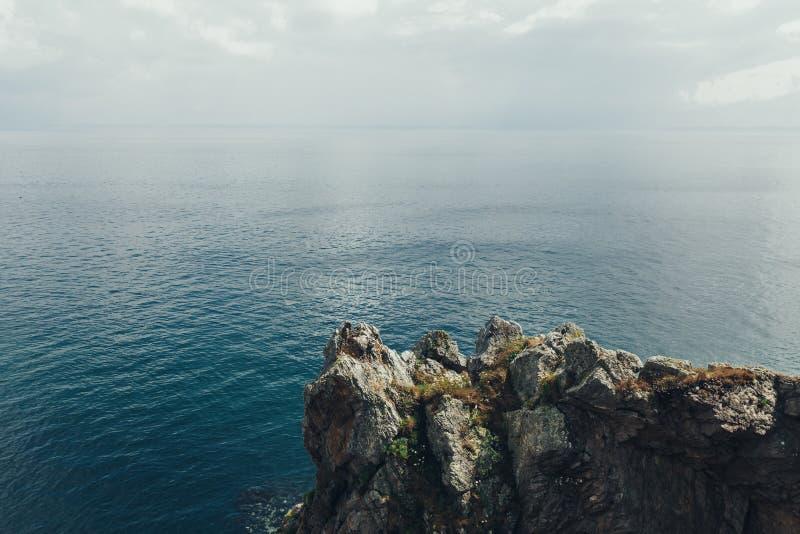 Os penhascos afiados penduram sobre o oceano, fundo marinho dramático imagem de stock
