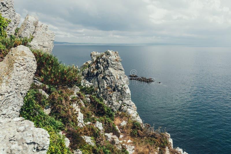 Os penhascos afiados penduram sobre o oceano, fundo marinho dramático fotos de stock royalty free