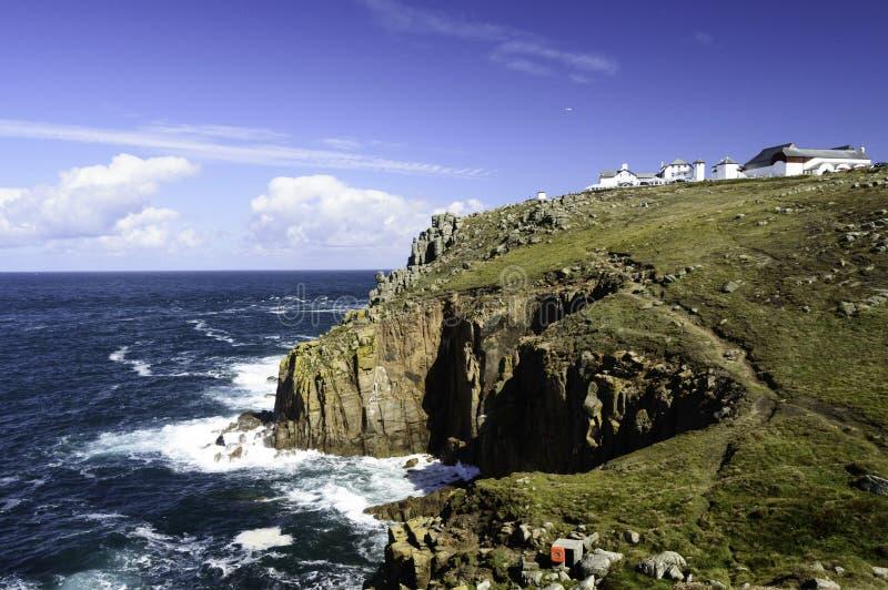 Os penhascos e as ondas de quebra em terras terminam em Cornualha fotografia de stock royalty free