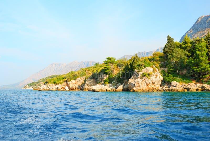 Os penhascos rochosos costeiam com as árvores verdes pelo mar imagem de stock
