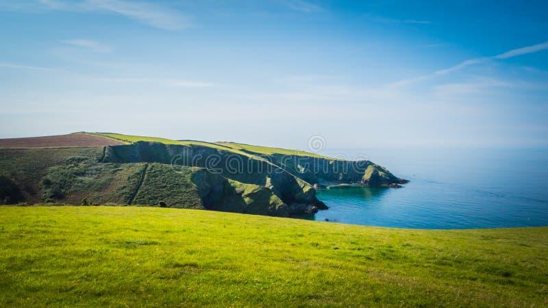 Os penhascos verdes bonitos ajardinam pelo Oceano Atlântico perto do cargo Isaac em Cornualha, Reino Unido imagem de stock
