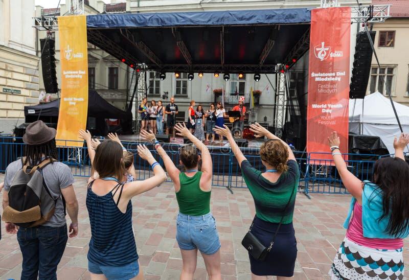 Os peregrinos do dia de juventude de mundo cantam e dançam no St Maria Magdalena Square em Cracow foto de stock royalty free