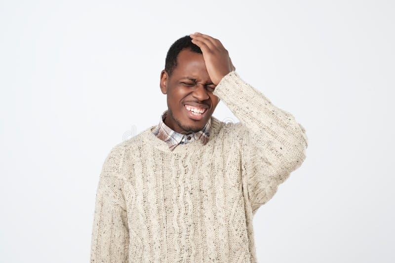 Os pesares lesam fazer Homem novo africano, golpeando a mão na cabeça no fundo cinzento imagens de stock