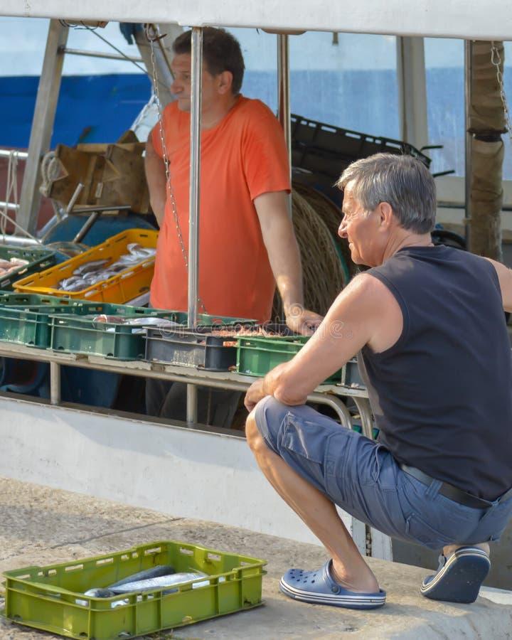 Os pescadores estão vendendo peixes recentemente travados no barco de pesca entrado no cais de Makarska, Croácia o 1º de junho imagens de stock