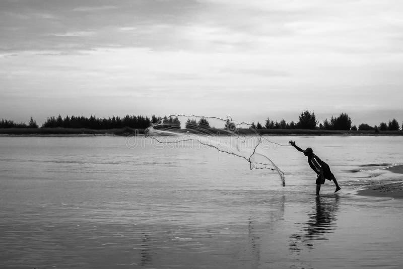 Os pescadores jogam uma rede de pesca para travar peixes fotos de stock