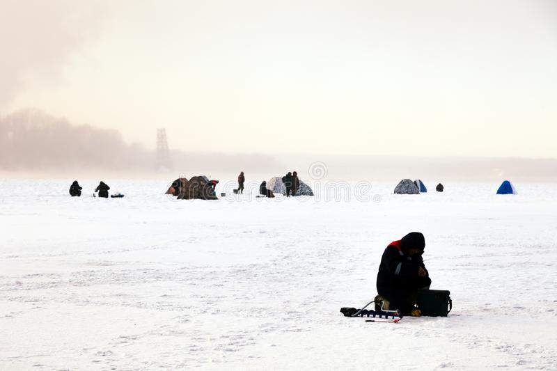 Os pescadores na pesca do inverno com barracas travam peixes no gelo Conceito do passatempo masculino, esporte, paixão, fim de se imagens de stock