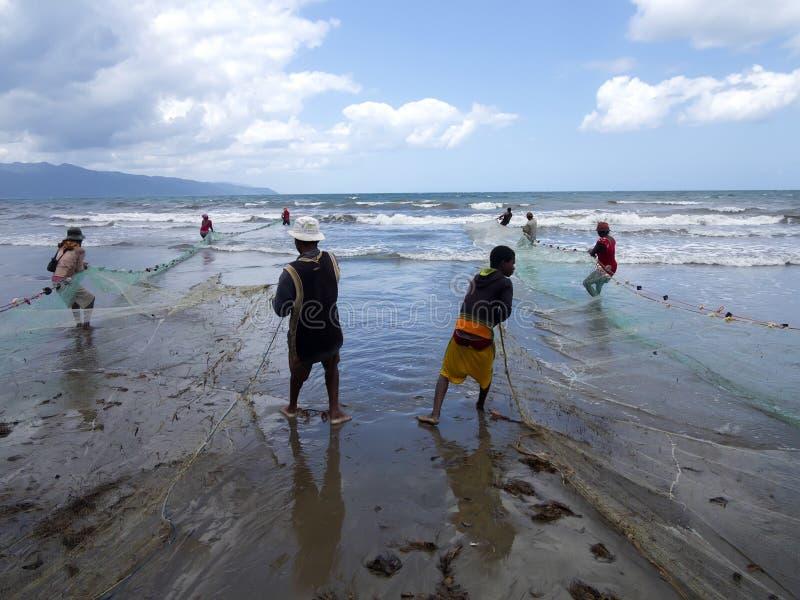 Os pescadores nativos puxam as redes, Antsiranana, Madagáscar imagem de stock