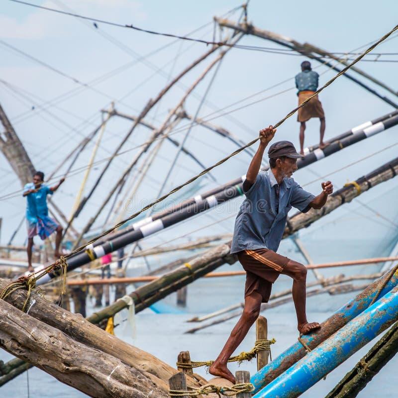 Os pescadores operam uma rede de pesca chinesa foto de stock royalty free