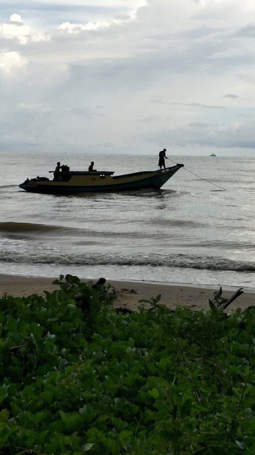 Os pescadores tradicionais começam a pescar O barco velho de pesca de madeira está a cruzar-se foto de stock royalty free
