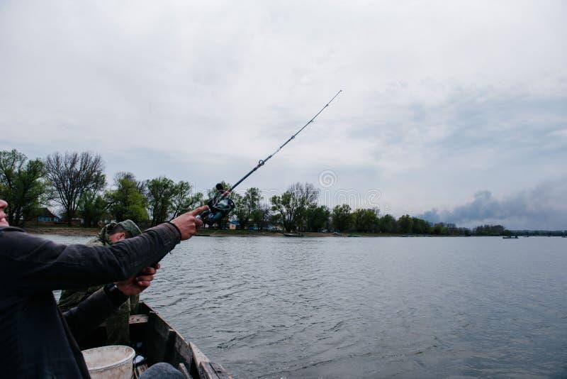 Os pescadores travam os peixes que sentam-se no barco fotografia de stock royalty free