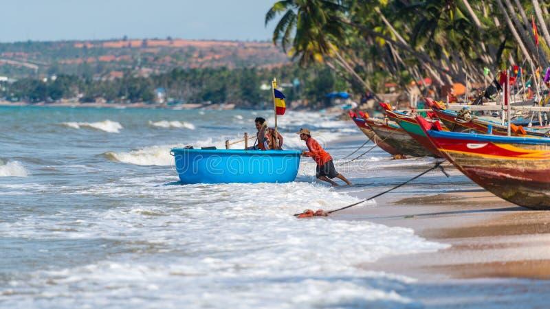 Os pescadores vietnamianos estão empurrando seu coracle da pesca para fora para o mar para seu dever diário no pescador Village,  imagens de stock