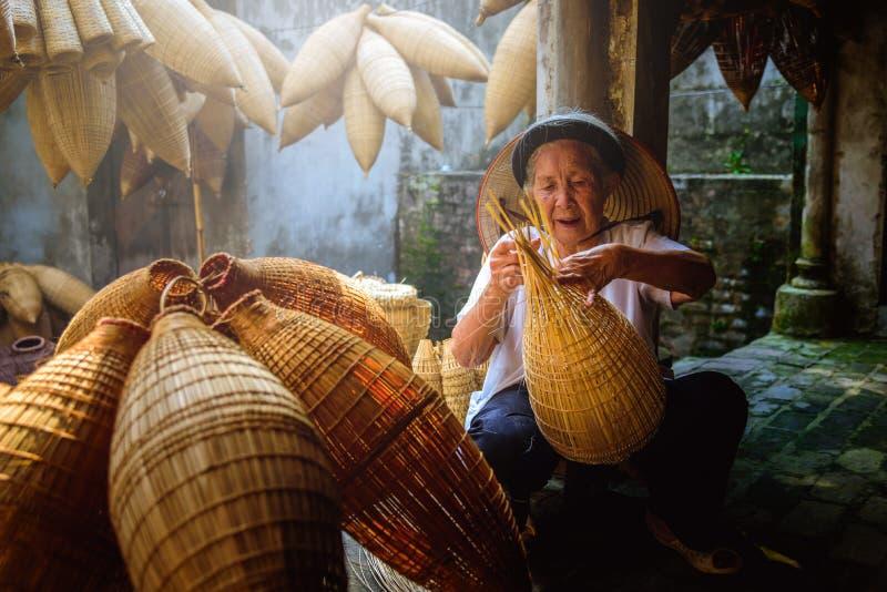 Os pescadores vietnamianos estão fazendo a cestaria para o equipamento de pesca em imagem de stock