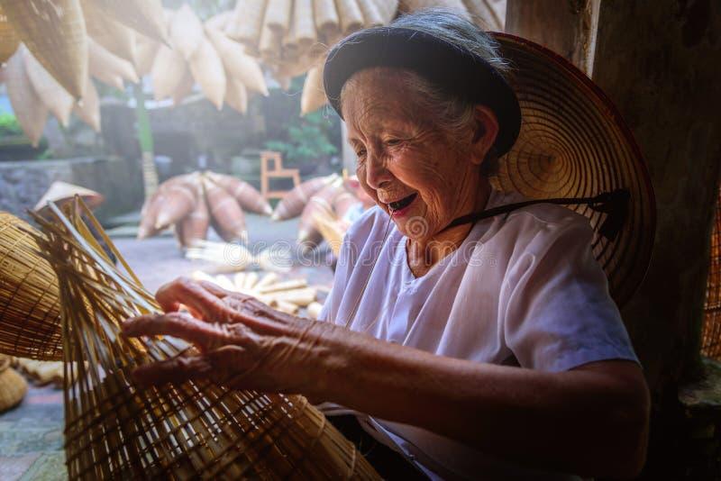 Os pescadores vietnamianos estão fazendo a cestaria para o equipamento de pesca em fotografia de stock