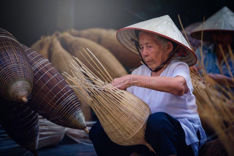Os pescadores vietnamianos estão fazendo a cestaria para o equipamento de pesca em imagem de stock royalty free