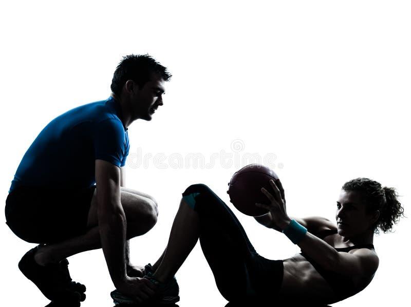 Os pesos de exercício da mulher do homem malham a silhueta da bola da aptidão fotografia de stock