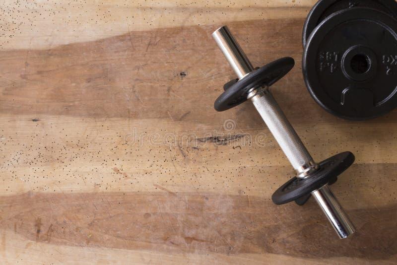 Os pesos e o peso ajustaram-se para a aptidão em um fundo de madeira fotos de stock