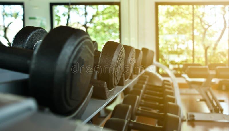 Os pesos encontram-se em seguido na cremalheira do inventário no gym ou no fitness center fotos de stock