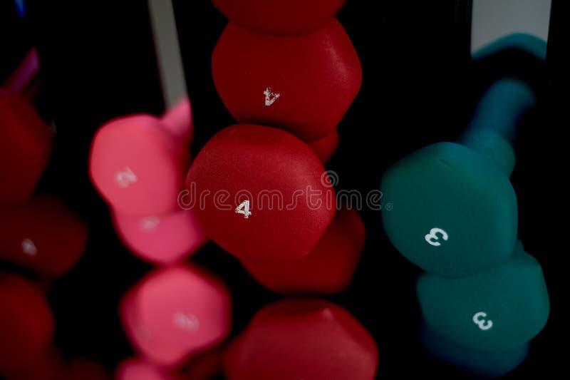 Os pesos são coloridos na cremalheira, com o baixo peso, classificado pela cor Sala da aptidão Imagem e esportes saudáveis foto de stock royalty free