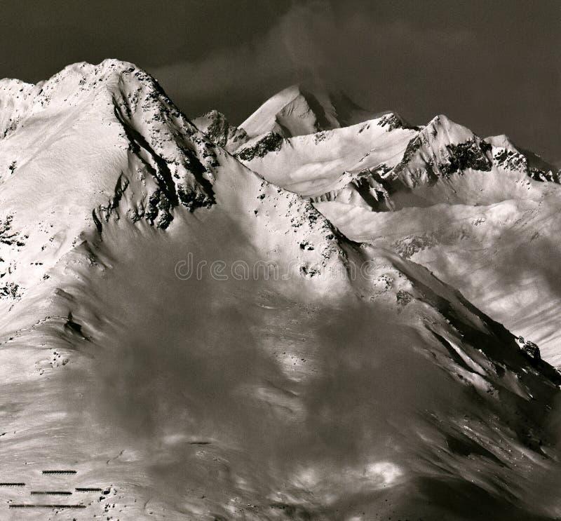 Os picos alpinos no desaparecimento nublam-se na manhã imagem de stock