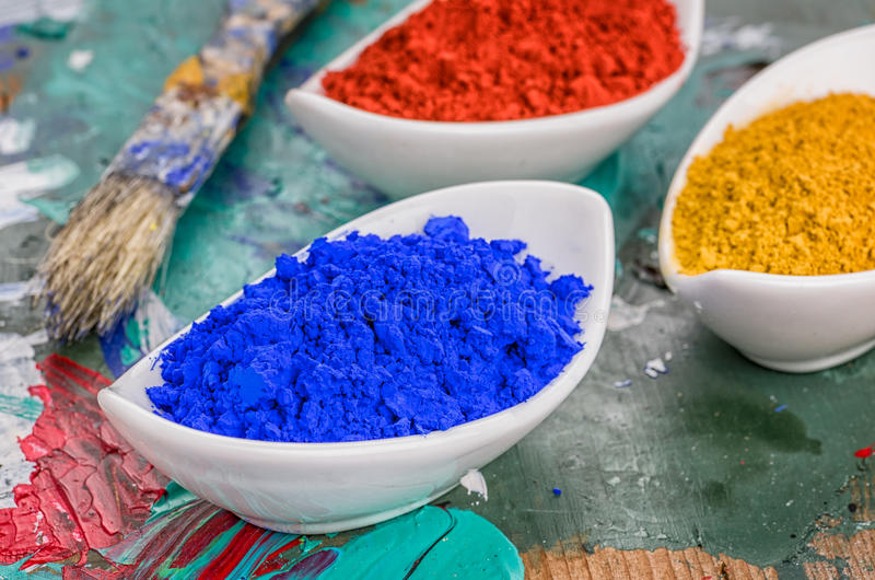 Os pigmentos vibrantes da cor na porcelana rolam em uma paleta de madeira fotografia de stock