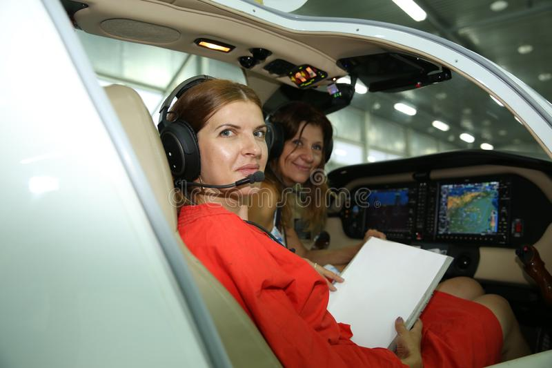Os pilotos das meninas nos fones de ouvido no esportes aplanam no aeroporto são um estilo de vida foto de stock royalty free