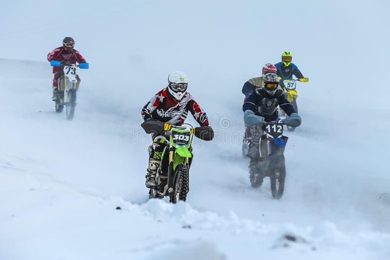 Os pilotos novos do grupo conduzem na trilha nevado do motocross fotos de stock royalty free