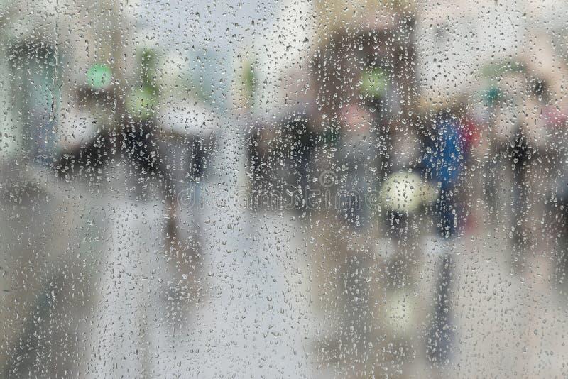 Os pingos de chuva no vidro de janela, pessoa andam na estrada no dia chuvoso, fundo borrado do sumário do movimento Conceito da  imagens de stock