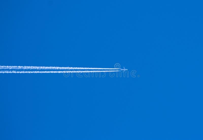 Os planos brancos das raias saem atrás como nuvens artificiais Fundo do c?u azul fotos de stock royalty free