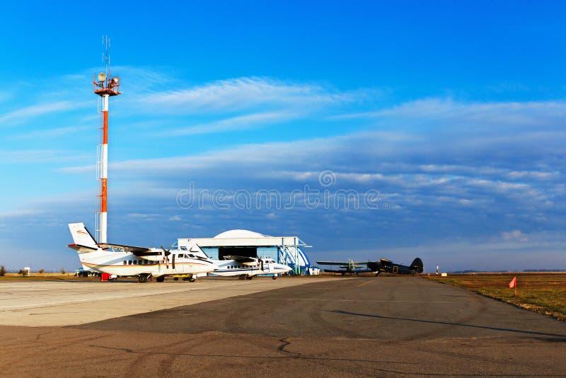 Os planos privados leves estacionaram no aeródromo, no aeródromo privado com hangar e na torre de comunicações foto de stock royalty free