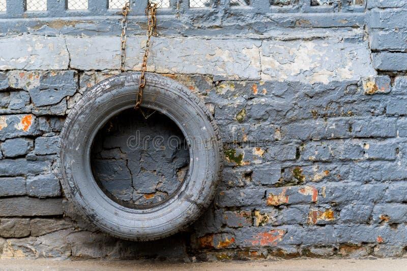 Os pneus coloridos que penduram na corrente têm uma parede de tijolo imagem de stock