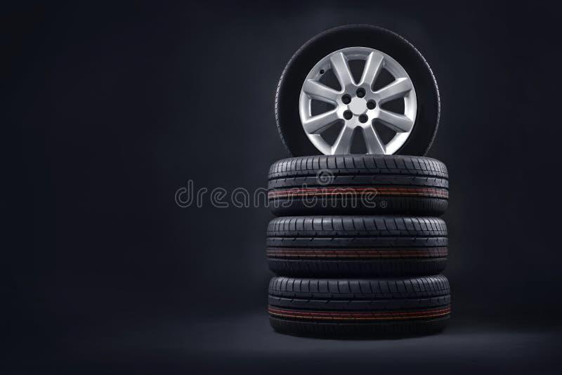 Os pneus novos empilham em um fundo escuro Fundo cabendo do pneu foto de stock royalty free